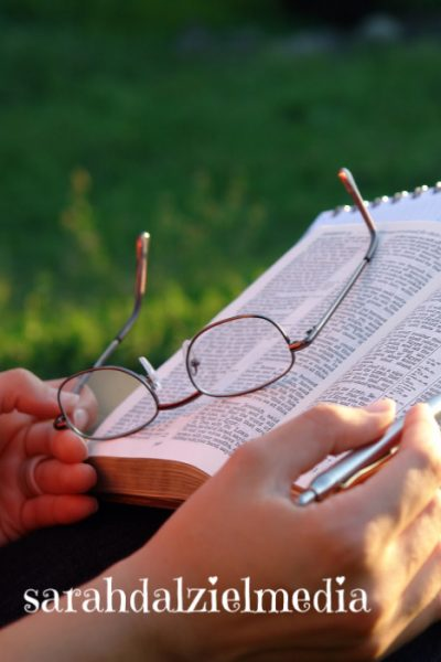 hands of a person holding a pen and glasses over an open bible
